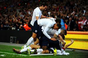 Steven Gerrard of England (obscured) celebrates with team mates as he scores their second goal during the FIFA 2014 World Cup Qualifying Group H match between England and Poland at Wembley Stadium on October 15, 2013 in London, England.  (Photo by Laurence Griffiths/Getty Images)