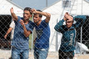 Migrants stand behind a fence at a camp after crossing the Macedonian-Greek border near Gevgelija on September 16, 2015. Migrants began to cross from Serbia into Croatia, desperate to find a new way into the European Union after Hungary sealed its border and a string of EU countries tightened frontier controls in the face of an unprecedented human influx. Pressure is building for a special EU summit to come up with solutions to the crisis, with the bloc bitterly split and free movement across borders -- a pillar of the European project -- in jeopardy, with Germany further calling it into question by boosting controls on parts of its frontier with France. AFP PHOTO / ROBERT ATANASOVSKIROBERT ATANASOVSKI/AFP/Getty Images