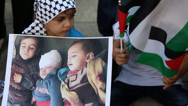 A Palestinian girl holds a poster that shows Palestinian kids who were killed in Gaza by Israeli airstrikes, as she attends a demonstration against the Israeli war in Gaza, in Beirut, Lebanon, Monday, July 21, 2014.  (AP Photo/Hussein Malla)
