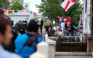 Protestors gather ahead of a parade on Woodvale Road, north Belfast as part of the annual Twelfth of July celebrations, marking the victory of King William III's victory over James II at the Battle of the Boyne in 1690. PRESS ASSOCIATION Photo. Picture date: Monday July 13, 2015. See PA story ULSTER Twelfh. Photo credit should read: Brian Lawless/PA Wire