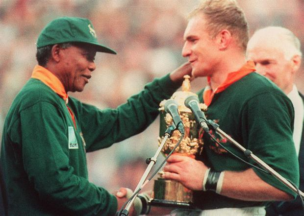 Springbok captain Francois Pienaar receives the Rugby World Cup from South African President Nelson Mandela at Ellis Park in Johannesburg on 24 June, 1995.