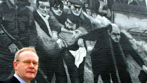 File photo dated 05/11/03 of Martin McGuinness walking past a Bloody Sunday mural in the Bogside in Derry. PA