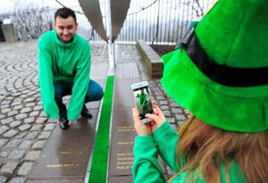 Ciara Kelly photographs Gareth Maguire on a mobile phone by the Meridian Line at the Royal Observatory in Greenwich, south east London, which is decorated green by Tourism Ireland to celebrate St Patrick's Day, which is on Tuesday 17th March.