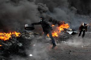 Protesters clash with police in central Kiev, Ukraine, Thursday Jan. 23, 2014. Thick black smoke from burning tires engulfed parts of downtown Kiev, as an ultimatum issued by the opposition to the president to call early election or face street rage was set to expire with no sign of a compromise on Thursday.  (AP Photo/Sergei Chuzavkov)