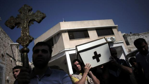 Palestinians carry the coffin of Christian woman Jalila Ayyad, 70, who was killed by an Israeli strike hit that destroyed her house, during her funeral at a church in Gaza City, Sunday, July 27, 2014.(AP Photo/Khalil Hamra)