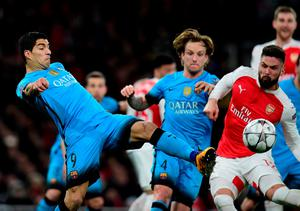 Barcelona's Uruguayan forward Luis Suarez (L) vies with Arsenal's French striker Olivier Giroud during the UEFA Champions League round of 16 1st leg football match between Arsenal and Barcelona at the Emirates Stadium in London on February 23, 2016.   / AFP / JAVIER SORIANOJAVIER SORIANO/AFP/Getty Images