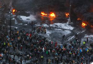 Tyres burn in the street, set alight by protesters in clashes with police in central Kiev, Ukraine, Wednesday, Jan. 22, 2014. Police in Ukraines capital on Wednesday tore down protester barricades and chased demonstrators away from the site of violent clashes, hours after two protesters died after being shot, the first violent deaths in protests that are likely to drastically escalate the political crisis that has gripped Ukraine since late November. (AP Photo/Sergei Grits)