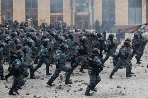 Helmeted riot police move in on hundreds of protesters in central Kiev, Ukraine, Wednesday, Jan. 22, 2014. Two people whose dead bodies were found Wednesday near the site of clashes with police have been shot with live ammunition, prosecutors said Wednesday, an announcement that could further fuel violence that spilled on the streets of the Ukrainian capital after two months of largely peaceful protests. (AP Photo/Evgeny Feldman)