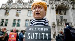 A man wearing a giant Boris Johnson mask, dressed as a prisoner, outside the Supreme Court in London, where judges have ruled that Prime Minister Boris Johnson's advice to the Queen to suspend Parliament for five weeks was unlawful. PA