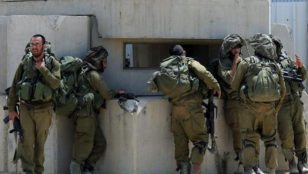 Israeli reserve soldiers rest at a stop near the Israel Gaza border after fighting in Khan Younis in the Gaza Strip on Wednesday, July 30, 2014. (AP Photo/Tsafrir Abayov)