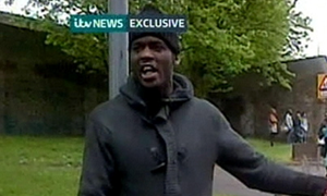 ITV News footage of a man holding weapons by the scene in John Wilson Street, Woolwich where a man was found murdered.