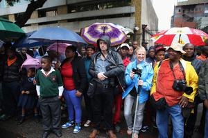 Media and locals brave the rain as they wait to try and get a glimpse of Oscar Pistorius as he leaves North Gauteng High Court at the end of the first day of his trial accused of the murder of his girlfriend Reeva Steenkamp on March 3, 2014 in Pretoria, South Africa. (Photo by Christopher Furlong/Getty Images)