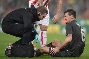 Liverpool's Croatian defender Dejan Lovren (R) receives treatment for an injury before being substituted in the first half during the English League Cup semi-final first leg football match at Britannia Stadium in Stoke-on-Trent, central England, on January 5, 2015.  AFP PHOTO / OLI SCARFF  RESTRICTED TO EDITORIAL USE. No use with unauthorized audio, video, data, fixture lists, club/league logos or 'live' services. Online in-match use limited to 75 images, no video emulation. No use in betting, games or single club/league/player publications.OLI SCARFF/AFP/Getty Images