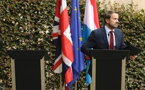 Luxembourg's Prime Minister Xavier Bettel, right, addresses a media conference next to an empty lectern intended for British Prime Minister Boris Johnson after a meeting at the prime ministers office in Luxembourg, Monday, Sept. 16, 2019. (AP Photo/Olivier Matthys)
