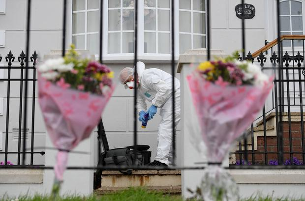 Police forensic experts and flowers at the murder scene. A man shot dead in west Belfast has been named as 57-year-old Kieran Wylie