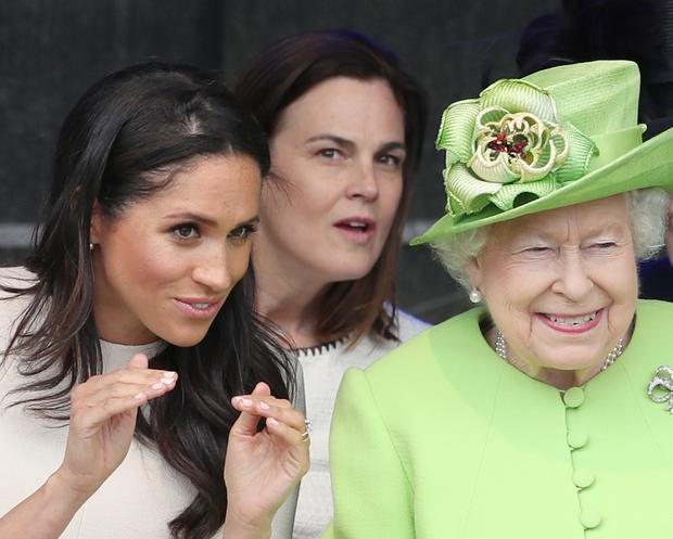 It has been alleged Samantha Cohen, in the centre behind Meghan and the Queen, was bullied by the duchess (Danny Lawson/PA)