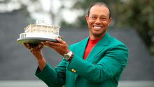 Pure class: Tiger Woods wearing the famous Green Jacket with the Masters trophy yesterday