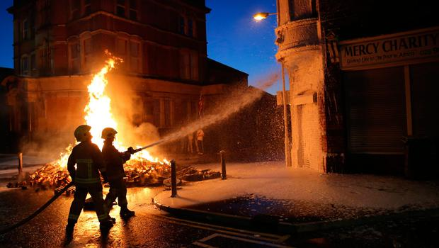 Firefighters douse nearby buildings as a bonfire is lit in Albertbridge Road, Belfast ahead of the key date in the protestant loyal order marching season - the Twelfth of July. PRESS ASSOCIATION Photo. Picture date: Tuesday July 11, 2017. See PA story ULSTER Twelfth. Photo credit should read: PA Wire