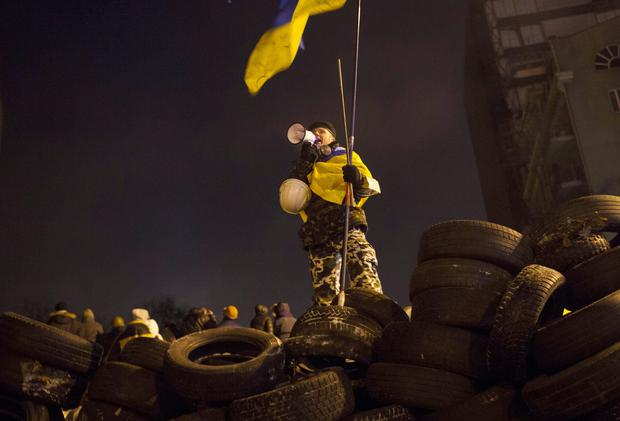 KIEV, UKRAINE - JANUARY 23: A protestor leads chants from on top of a wall of tires on January 23, 2014 in Kiev, Ukraine. Talks to resolve the political stalemate in the Ukraine have failed as anti-government protests continue in the capital and opposition leader Vitali Klitschko urges the government to call a snap election. (Photo by Rob Stothard/Getty Images)