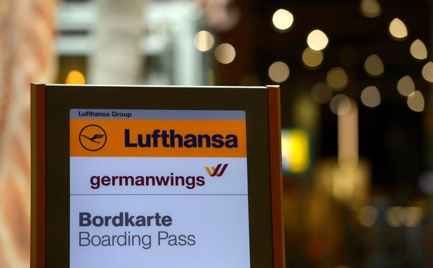 The logo of German airline Lufthansa (top) and its Germanwings subsidiary can be seen near a counter on March 24, 2015 at the airport in Duesseldorf, western Germany, where the crashed Germanwings airplane was due to land.