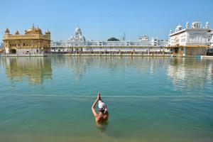 An Indian Sikh youth takes a dip in the holy sarover (water tank) at The Golden Temple in Amritsar on April 9, 2015 on the occasion of the 394th anniversary of the birth of the ninth Sikh Guru, Teg Bahadur.  Guru Tegh Bahadur, the youngest of the five sons of Guru Hargobind, was born in Amritsar in 1621 and was executed on the orders of Mughal Emperor Aurangzeb in Delhi in 1675.  AFP/Getty Images