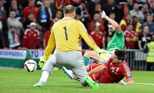 Northern Ireland's striker Stuart Dallas (R) has his shot saved by Hungary's goalkeeper Gabor Kiraly (L) as Hungary's defender Richard Guzmics slides in to block during the Euro 2016 qualifying group F football match between Northern Ireland and Hungary at Windsor Park in Belfast on September 7, 2015. AFP PHOTO / MICHAEL COOPERMichael Cooper/AFP/Getty Images