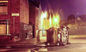 A stolen car toppled in the Beechmount Street area of west Belfast following a car chase. Pic Kevin Scott