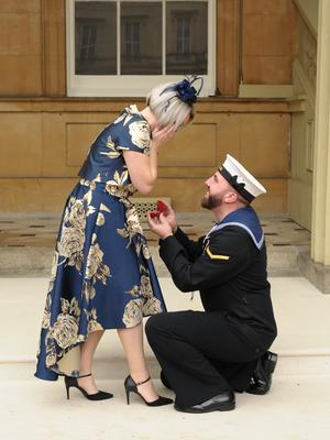 Matthew Gallimore proposes to Adele Thomasson in the Quadrangle of Buckingham Palace (Fiona Stapley-Harding/PA)