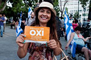A woman celebrates at Klafthmonos Square in Athens on July 5, 2015 after the first exit-polls of the Greek referendum. A referendum to decide whether or not Greece will accept the bailout conditions proposed jointly by the European Commission, the International Monetary Fund and the European Central Bank took place on July 5, with initial polls suggesting the Greek country not wanting to pay back their creditors.  AFP PHOTO / IAKOVOS HATZISTAROUIAKOVOS HATZISTAVROU/AFP/Getty Images