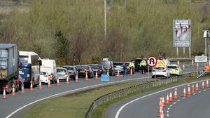 Gardai including armed detectives mount coronavirus checkpoints on the border with Northern Ireland at Carrickarnon, Co Louth (Niall Carson/PA)