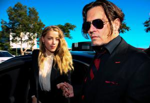 US actor Johnny Depp (R) and his wife Amber Heard arrive at a court in the Gold Coast on April 18, 2016.  Depp and Heard arrived at an Australian court April 18 over Heard's alleged illegal importation of their two Yorkshire terrier dogs Boo and Pistol into the country in a private jet in 2015, as Depp was in Australia for the filming of the latest Pirates of the Carribean movie.    / AFP PHOTO / Patrick HAMILTONPATRICK HAMILTON/AFP/Getty Images