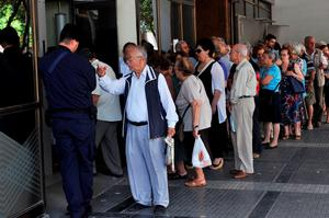 Pensioners wait outside a National Bank branch in Thessaloniki on July 2, 2015, as banks only opened to allow pensioners without bank cards to withdraw 120 euros ($133) from their pensions to last them the rest of the week. Amid capital controls and lines of customers withdrawing as much cash as limits allow, the National Bank of Greece on July 2 stressed it was accepting euro deposits at all its ATMs. Greece's radical left government suggested it would resign if it fails to get its way in a make-or-break referendum July 5 that could decide the country's financial future. AFP PHOTO / SAKIS MITROLIDISSAKIS MITROLIDIS/AFP/Getty Images