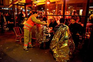 PARIS, FRANCE - NOVEMBER 13:  Survivors are tended to at a cafe after gunfire in the Bataclan concert hall on November 13, 2015 in Paris, France. According to reports, over 150 people were killed in a series of bombings and shootings across Paris, including at a soccer game at the Stade de France and a concert at the Bataclan theater.  (Photo by Antoine Antoniol/Getty Images)