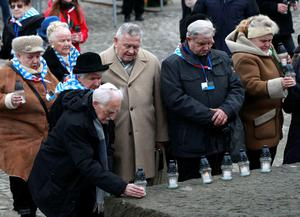 Survivors put down candles during a ceremony at the former Auschwitz Nazi death camp in Oswiecim, Poland, Wednesday, Jan. 27, 2016, the 71st anniversary of the death camp's liberation by the Soviet Red Army in 1945.  (AP Photo/Czarek Sokolowski)