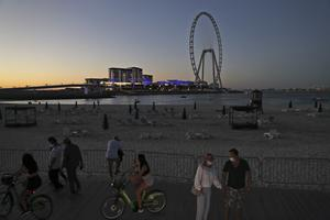 Tourists and residents enjoy the sunset at the Jumeirah Beach Residence, in Dubai (Kamran Jebreili/AP)