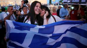 "ATHENS, GREECE - JULY 05:  People celebrate in front of the Greek parliament as early opinion polls predict a win for the Oxi, or No, campaign in the Greek austerity referendum. Crowds are begining to gather in the squares of Athens waiting for the official result on July 5, 2015 in Athens, Greece. The people of Greece went to the polls to decide if the country should accept the terms and conditions of a bailout with its creditors. Greek Prime Minister Alexis Tsipras is urging people to vote ""a proud no"" to European creditors' proposals, and ""live with dignity in Europe"". 'Yes' campaigners believe that a no vote would mean financial ruin for Greece and the loss of the Euro currency.  (Photo by Christopher Furlong/Getty Images)"