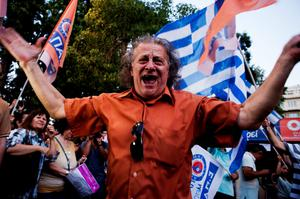 A man celebrates at Klafthmonos Square in Athens on July 5, 2015 after the first exit-polls of the Greek referendum. A referendum to decide whether or not Greece will accept the bailout conditions proposed jointly by the European Commission, the International Monetary Fund and the European Central Bank took place on July 5, with initial polls suggesting the Greek country not wanting to pay back their creditors.  AFP PHOTO / IAKOVOS HATZISTAROUIAKOVOS HATZISTAVROU/AFP/Getty Images