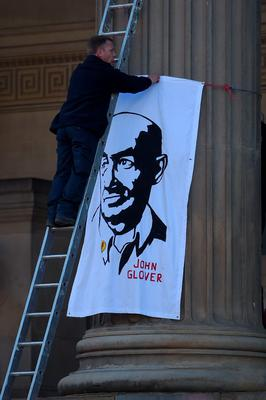 A man fixes a banner depicting an image of John Glover, who lost his son Philip Glover in the 1989 Hillsborough disaster, as people gather to pay their respects outside St Georges Hall in Liverpool, north west England on April 27, 2016, in remembrance of the 96 Liverpool fans who died in the 1989 Hillsborough football stadium disaster. Thousands of sympathisers were expected to pay an emotional tribute to the Hillsborough disaster victims today after a landmark inquest found that 96 Liverpool football fans were unlawfully killed. John Glover died before the inquest. / AFP PHOTO / PAUL ELLISPAUL ELLIS/AFP/Getty Images