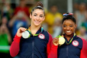 RIO DE JANEIRO, BRAZIL - AUGUST 16:  Silver medalist Alexandra Raisman (L) and gold medalist Simone Biles (R) of the United States pose for photographs on the podium at the medal ceremony for the Women's Floor on Day 11 of the Rio 2016 Olympic Games at the Rio Olympic Arena on August 16, 2016 in Rio de Janeiro, Brazil.  (Photo by Alex Livesey/Getty Images)