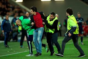 A security holds a man who entered a pitch during the UEFA Champions League quarter-final, first-leg football match between VfL Wolfsburg and Real Madrid on April 6, 2016 in Wolfsburg, northern Germany.  / AFP PHOTO / RONNY HARTMANNRONNY HARTMANN/AFP/Getty Images