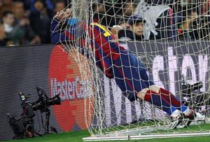 Barcelona's Argentinian forward Lionel Messi holds the goal net during the UEFA Champions League round of 16 football match FC Barcelona vs Manchester City at the Camp Nou stadium in Barcelona on March 18, 2015. AFP PHOTO / QUIQUE GARCIAQUIQUE GARCIA/AFP/Getty Images