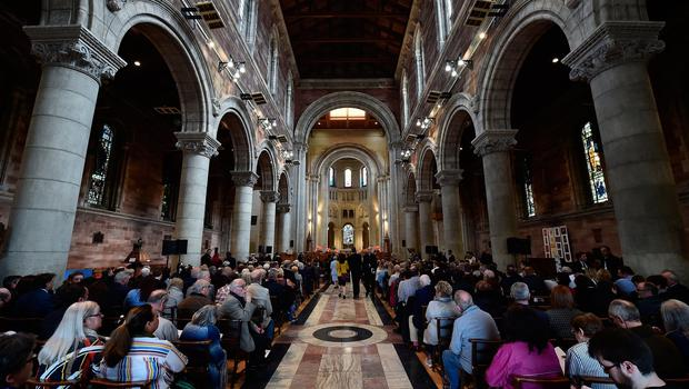 """BELFAST, NORTHERN IRELAND - APRIL 24:  The congregation arrive for the funeral service of journalist Lyra McKee at St Annes Cathedral on April 24, 2019 in Belfast, Northern Ireland. Journalist and campaigner for LGBT rights, Lyra McKee, 29, was shot dead last Thursday while observing the rioting in Londonderry. Her family gave a statement in which they said her """"openness and her desire to bring people together made her totally apolitical"""". The New IRA have admitted responsibility for her killing. (Photo by Charles McQuillan/Getty Images)"""