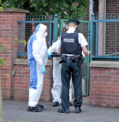 A police officer and forensic experts carry out a search at Maeve House in the New Lodge area of north Belfast, where Semtex was discovered on Monday