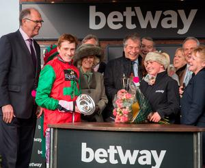The Duchess of Cornwall (third left)makes a presentation to the owners and jockey Sam Twiston-Davies , of the winning horse in the Betway Queen Mother Champion Steeple Chase, on Ladies Day during the Cheltenham Festival at Cheltenham Racecourse. PRESS ASSOCIATION Photo. Picture date: Wednesday March 11, 2015. See PA story RACING Cheltenham. Photo credit should read: Matt Cardy/PA Wire