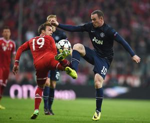 MUNICH, GERMANY - APRIL 09: Wayne Rooney of Manchester United is challenged by Mario Goetze of Bayern Muenchen during the UEFA Champions League Quarter Final second leg match between FC Bayern Muenchen and Manchester United at Allianz Arena on April 9, 2014 in Munich, Germany.  (Photo by Lars Baron/Bongarts/Getty Images)