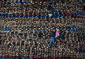 BELFAST, NORTHERN IRELAND - JULY 11: A Loyalist poses for a drone as he is filmed making final preparations to a huge bonfire on the Ballymacash estate on July 11, 2016 in Belfast, Northern Ireland. The Ballymacash bonfire is reported as the largest bonfire construct in the province. The lighting of the bonfires at midnight on the eleventh night marks the start of the annual twelfth of July celebrations within the protestant community. The Orange marches and demonstrations celebrate the Battle of the Boyne in 1690 when the Protestant King William of Orange defeated the Catholic King James II on the banks of the river Boyne. (Photo by Charles McQuillan/Getty Images)