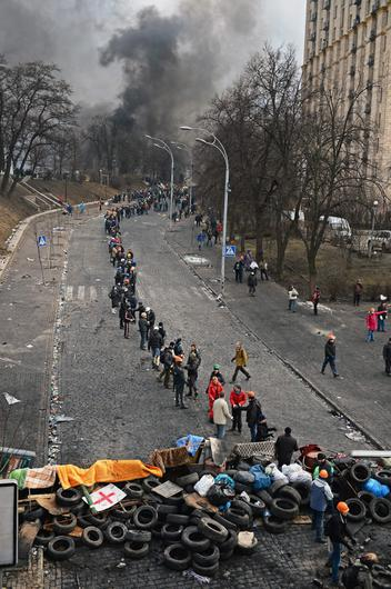 KIEV, UKRAINE - FEBRUARY 20:  Anti-government protesters form a human chain as they carry rocks and tyres to rebuild barricades following continued clashes with police in Independence square, despite a truce agreed between the Ukrainian president and opposition leaders on February 20, 2014 in Kiev, Ukraine. After several weeks of calm, violence has again flared between police and anti-government protesters, who are calling to oust President Viktor Yanukovych over corruption and an abandoned trade agreement with the European Union  (Photo by Jeff J Mitchell/Getty Images)