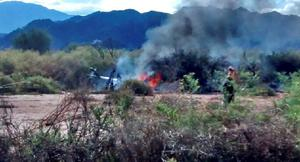 Picture released by NA showing the wreckage of a helicopter burning in flames after colliding mid-air with another chopper near Villa Castelli, in the Argentine province of La Rioja, on March 9, 2015. All ten people aboard the helicopters died, including a French reality show cast, according to the provisional government.