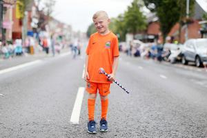 Press Eye - Belfast -  Northern Ireland - 13th July  2015  Belfast's Orange Order annual 12th of July demonstration makes its way through the City Centre to the field at Malone House beside Shaws Bridge.  Seven-year-old Marcus Toan waits for the parade on the Lisburn Road.   Picture by Jonathan Porter/Press Eye