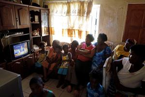 A family watch a television showing the funeral service of former South African President Nelson Mandela at their home in the Soweto township, Johannesburg, South Africa, Sunday, Dec. 15, 2013.  (AP Photo/Markus Schreiber)